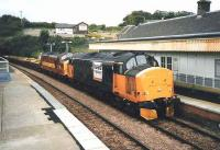 Loadhaul and EWS liveried class 37s haul an up ballast train through North Queensferry in July 1999 with the station in the process of being repainted.<br><br>[David Panton&nbsp;/07/1999]