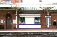 Traditionally a well kept station, a section of the down platform at Dumfries shows an interesting selection of <I>platform furniture</I> in May 2008. On the left above the wooden bench is a notice marking Dumfries as <I>Best Station 1987</I>. A tub of plants stands alongside the booking office door. An old platform kiosk, recently repainted, is being used to display art works. The former platform drinking fountain is on the right, with a red pillar box standing alongside. As for the canopy...<br><br>[John Furnevel&nbsp;20/05/2008]