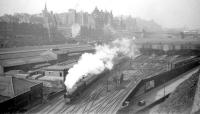 View over the east end of Waverley in the early 60s with an ECML train leaving for the south. To the left of the train, the East box, New Street bus depot and the various railway buildings and sidings have all gone with the new Edinburgh Council headquarters now occupying much of the area. <br><br>[Robin Barbour Collection (Courtesy Bruce McCartney)&nbsp;//]