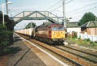 The morning Powderhall - Oxwellmains <I>Binliner</I> containers run east through Prestonpans in June 1999 behind 56 059. <br><br>[David Panton&nbsp;/06/1999]