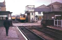 Looking east towards Blackburn from Bamber Bridge station in September 1978 as a pair of Cravens DMUs pass on the Preston - Colne route. The buildings at the end of the platforms on either side of the level crossing gave access to a pedestrian subway. The subway was filled in and the associated structures demolished in 2005/6. The signal box still stands but nowadays controls only this crossing and another at nearby Hospital Inn. <br><br>[Mark Bartlett&nbsp;/09/1978]