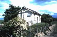 The old station building at Saltoun on the Gifford branch June 1985. Closed to passengers as early as 1933, the line continued in use to here for freight until 1965. The station building looks as though it had been put to alternative use since closure, as indicated by the sign on the side which reads...<I>Agricultural Premises - Used by Brucellosis Accredited Cattle - No Dogs or Horses Please - Disinfect Feet.</I> [Brucellosis was erradicated amongst UK herds in 1979 - although it has since been reintroduced on several occasions by imported cattle!] <br><br>[David Panton&nbsp;07/06/1985]