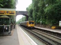 Situated in a deep cutting, Aughton Park station opened in 1907, almost 60 years after the line itself. The ticket office is at street level to the right of the bridge, well above the platforms. 507007 arrives on a Liverpool - Ormskirk service on 29 June. <br><br>[Mark Bartlett&nbsp;28/06/2008]