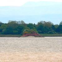 The south shore of the Solway Firth, looking across the gap where once stood the Solway Viaduct, seen from the Annan embankment on 21 May 2008. The southern embankment is much longer than its northern equivalent and still contains a single set of the linked iron piers [see image 17192] that once supported the structure. Just beyond the trees stands the impressive former station of Bowness-on-Solway, now a private house. The Cumbrian Fells dominate the skyline.<br><br>[John Furnevel&nbsp;21/05/2008]