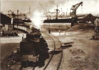 Caledonian Dock Shunter 56329 at King George V Dock with a train load of coal. The crane in the background belongs to the Barclay Curle shipyard in Whiteinch. The photo dates from the 1950s and is part of RailPhotoPrint postcard series. <br><br>[Graham Morgan Collection&nbsp;//]