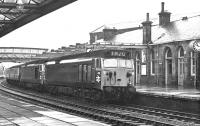A short, sharp shower of rain sweeps across Dumfries during the morning of 24 March 1972. With electrification work in full swing on the WCML, locomotives 409+433 bring train 1M20, the diverted up <I>Royal Scot</I>, south through the station.<br><br>[John Furnevel&nbsp;24/03/1972]