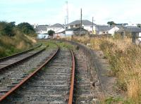 The abandoned Stranraer Town station in August 2003 looking west towards Portpatrick. The boarded up station building still stands in the background. Stranraer Town closed to passengers in March 1966.<br><br>[John Furnevel&nbsp;17/08/2003]