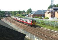 A Glasgow Central - Carlisle DMU south of Dumfries station in May 2003. The building on the right is the headquarters of Dumfries and Galloway Police, standing on the site once occupied by Dumfries locomotive shed. [See image 45214]<br><br>[John Furnevel&nbsp;11/05/2003]