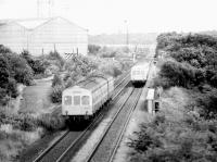 DMUs meet at Gartcosh in 1980. The rolling mill and sidings are on the left, Gartcosh Junction and signal box can just be seen in the background above the train on the right. This is the approximate site of the new Gartcosh station opened on 9 May 2005. [See image 16718]<br><br>[John Furnevel&nbsp;02/05/1980]