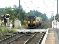 Looking west over Kirknewton level crossing in September 2002 as a train leaves for Glasgow Central.<br><br>[John Furnevel&nbsp;03/09/2002]