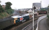 1977 was the Queens Jubilee year and Stratford MPD's contribution was to apply Union Jacks to the sides of 47163 and 47164. The latter is seen here departing Norwich Thorpe for London in June 1977. Sister engine 47163 was involved in a fatal collision later that year. The signal box lasted until August 1988. <br><br>[Mark Dufton&nbsp;27/06/1977]