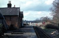 The Midland and Great Northern railway architecture was very characteristic and attractive. At the time of this photo, in February 1977, Lenwade was the last example of a fully equipped M&GN station that was substantially intact and still operational for goods. One hoped that when regular freight traffic petered out at the end of 1981, some serious preservation attempt would be made. What one got initially included a stockade built round the station, <I>Keep Out</I> notices and a vicious sounding dog to guard it. Although the trackwork and accessories have now largely gone, the building and platform still remain alongside <I>Marriotts Way</I>.<br><br>[Mark Dufton&nbsp;13/02/1977]