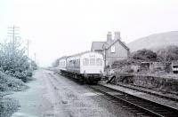 A Met Cam 101 DMU in hybrid livery calls at Llwyngwril on a Pwllheli service in May 1980. The passing loop had been removed by this time. Judging by the arm waving this was a school service. View north towards Barmouth. <br><br>[Mark Bartlett&nbsp;/05/1980]