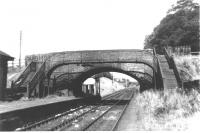 View east through Towers Road bridge at Clarkston (Lanarks) station on the eastern outskirts of Airdrie, looking towards Bathgate in 1962. Note the locomotive watering facilities just beyond the end of the platform. The station closed to passengers in January 1956. [See image 33178] <br><br>[Colin Miller&nbsp;//1962]