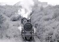 Standard class 4 2-6-0 No 76114 of Corkerhill shed leaving Braehead power station sidings and approaching Deanside with coal empties in 1966. Taken from the old Renfrew - Glasgow road which was cut when the KGV dock opened (Deanside station is behind the camera). The last of its class, 76114 was the last steam locomotive built at Doncaster works, having been completed there on 16 October 1957. <br><br>[Colin Miller&nbsp;//1966]