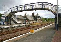 Looking across the tracks towards the southbound (truncated) platform at Lairg on 31 August 2007, just prior to the downpour. The former station building, now in private ownership, stands beyond the large modern platform shelter, with one of the holding tanks of the rail-served Lairg oil terminal, located behind the station, visible just beyond in the background. <br><br>[John Furnevel&nbsp;31/08/2007]