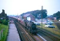One of the 852 Stanier 8F 2-8-0s to be built, no 48033 of Sutton Oak shed, St Helens (8G), coasts south through Ravenglass station on the Cumbrian Coast with a lengthy freight circa 1966. The passing locomotive receives a greeting from a gathering of children (presumably part of a school trip) waiting on the northbound platform. The terminus of the adjacent Ravenglass & Eskdale Railway can be seen on the right.<br><br>[Robin Barbour Collection (Courtesy Bruce McCartney)&nbsp;//1966]