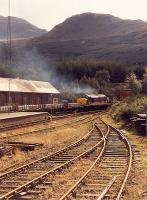 A 37 with aluminium slabs makes a smoky departure for the south from Crianlarich.<br><br>[Ewan Crawford&nbsp;//1990]