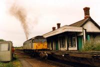 A 47 passes through the well preserved Felixstowe Beach station in 1990 with a container train. The unpreposessing cabin on the left was the signalbox.<br><br>[Ewan Crawford&nbsp;//1990]