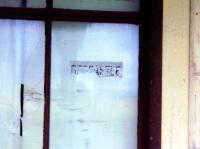 One of the old waterslide transfers [see image 20678] intended for flat - plate gas lamps attached to a window at the remains of the Highland Railway Redcastle station on the Fortrose branch in 1990. Redcastle station closed to passengers in October 1951.<br><br>[Colin Miller&nbsp;//1990]