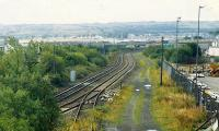 This view looks towards Fouldubs from the site of Grangemouth station. From left to right: lifted lines, lines to the oil terminal, former yards and docks, the site of Grangemouth No 3 box, out of use line (now lifted) to the docks (centre bottom) and the site of Grangemouth station. This was taken not long after removal of the box when signalposts still stood and the double track line had become two single track lines splitting at Fouldubs. The footbridge in the distance has been removed. (Compare with images 20698 and 7369).<br><br>[Ewan Crawford&nbsp;//1989]