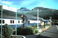 The southbound sleeper from Fort William stands at Crianlarich on a Summer evening in 1985 hauled by a class 37 locomotive accompanied by an ETHEL unit.<br><br>[Colin Alexander&nbsp;//1985]
