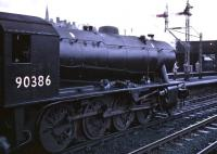 Austerity 2-8-0 90386 stands at Stirling on 11 April 1966 with the SLS/BLS/SLPF <I>Scottish Rambler No 5</I> railtour. The locomotive had brought the train up from Queen Street and was in the process of handing over to J38 65914 for the next stage of the journey, a circuitous route to Bathgate Junction.<br><br>[Robin Barbour Collection (Courtesy Bruce McCartney)&nbsp;11/04/1966]