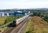 A Pendolino being dragged south on 28 September 2008 past the site of the former Royal Ordnance Factory at Euxton, Lancs (also known as ROF Chorley). The large factory stood to the left of the tracks with office and administrative facilities to the right. The location boasted its own station, opened in 1938 as Chorley ROF Platform and renamed Chorley Halt by 1942. The station was closed by 1963 and subsequently demolished after the majority of the site had been redeveloped for housing and commercial use. Island platform remains can be seen to the right of the tracks on the weed covered mound.<br> <br><br>[John Mcintyre&nbsp;28/09/2008]
