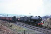 J38 65914 stands at Kinneil alongside the <I>Scottish Rambler No 5</I> Railtour on 11 April 1966 having brought the train in from Stirling where it took over from Austerity 90386 [see image 20904]. View is west towards Grangemouth. The fenced-off area on the right was a coal stocking yard, shunted by an NCB Pug.<br><br>[Robin Barbour Collection (Courtesy Bruce McCartney)&nbsp;11/04/1966]