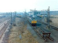 The locomotive facilities serving the massive coal concentration hump yard at Wath (BR shed code 41C), between Barnsley and Doncaster, in February 1981. The yard opened in 1907 and, at its peak, served no less than 45 collieries operating within a 10 mile radius of the site. As well as diesel locomotives, several EM1 electrics built to haul the heavy coal trains west over the Pennines via Woodhead Tunnel can be seen. The Woodhead route closed less than 6 months after this picture was taken, with the last train running over the line on 17 July 1981. Wath shed was eventually closed in 1983 and the yard itself in 1988, along with the last of the local collieries.<br><br>[Colin Alexander&nbsp;01/02/1981]