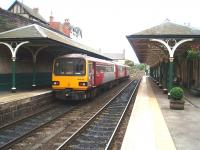 Knaresborough station looking towards Harrogate as 3-car 144020 waits to depart for Leeds. Beyond the train the crossover on the Nidd viaduct can be seen. A fireplace business occupies most of the buildings on the York platform, and the station is in excellent condition. <br><br>[Mark Bartlett&nbsp;11/10/2008]