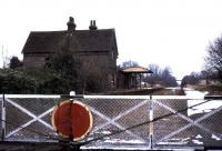 Looking north over the level crossing in Station Road, Isfield, Sussex in 1974. The view is towards Uckfield, to where the line was cut back in 1969, resulting in the closure of Isfield station. On a brighter note the site is now the HQ of <i>The Lavender Line</i> preservation group, while there is growing pressure for the reopening of the through route between Uckfield and Lewes.<br><br>[Ian Dinmore&nbsp;//1974]
