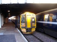 An Edinburgh - Aberdeen service, formed by 158712, peeps out from below the bridge at Arbroath station on 12 February 2008 and is reflected in the coaches of a National Express HST set standing in the adjacent platform.<br><br>[Sandy Steele&nbsp;12/02/2008]
