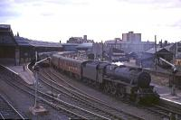 A busy scene at Perth in August 1965 as Stanier Black 5 No 44718 pulls in with a Dundee - Glasgow train while a down service boards at the opposite platform. A type 2 diesel locomotive is standing between the trains on the centre road.<br><br>[G W Robin&nbsp;28/08/1965]