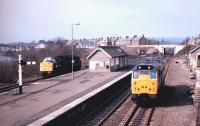 A class 31 heading west towards Newcastle on the N&C main line in the Autumn of 1984 passes 40056 standing alongside the Alston platform at Haltwhistle station.<br> <br><br>[Colin Alexander&nbsp;//1984]