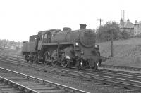 BR Standard Class 4 no 76091 passes Corkerhill shed heading for Glasgow in 1963. Part of the 1896 G&SW Corkerhill Railway Village can be seen in the left background behind the signal box. 76091 moved to Hurlford some months later and was withdrawn from there in December of 1966. End of the road was at Shipbreaking Industries, Faslane, the following April.<br> <br><br>[Colin Miller&nbsp;//1963]