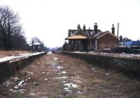 The derelict station at Isfield, Sussex, in the winter of 1974, almost 5 years after closure. View south towards the level crossing and the former through route to Lewes. [See image 40376] <br><br>[Ian Dinmore&nbsp;//1974]
