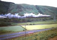 An 11 coach train climbs Beattock with the assistance of a banking locomotive in the early 1960s. A very quiet A74 runs past in the foreground.<br><br>[Robin Barbour Collection (Courtesy Bruce McCartney)&nbsp;//]