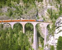 An eastbound <I>Glacier Express</I> for St. Moritz crosses the Landwasser Viaduct on the RhB network near Filisur in August 1998. The train is about to enter Landwasser Tunnel by the famous western portal where the viaduct meets a vertical cliff face.<br> <br><br>[Fraser Cochrane&nbsp;/08/1998]
