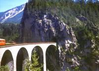 The western portal of Landwasser Tunnel showing the viaduct meeting the cliff face, taken from a westbound train in August 1998. To the left of the picture is a flat wagon and the last coach of the train.<br> <br><br>[Fraser Cochrane&nbsp;/08/1998]