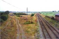 Site of the former Crosshouse station, Ayrshire, in August 1974, just over 8 years after closure. The route north west towards Dalry lies straight ahead, while the trackbed on the left once carried the line to Irvine.<br><br>[Colin Miller&nbsp;11/08/1974]