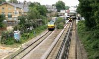 Looking east towards Highbury & Islington station NLL platforms in July 2005. A Richmond - North Woolwich <I>Silverlink</I> service stands at the eastbound platform, while a westbound freight runs past the station. The interchange links provided here, serving passengers on the North London Line, Victoria Line and Northern City Line will be further extended when the station becomes the new northern terminus of phase one of the East London Line extension in 2010. The London Borough of Islington is currently considering redevelopment of the station, including building a large office/retail block over the current station site.<br><br>[John Furnevel&nbsp;22/07/2005]