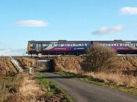 Just to the Lytham side of Moss Side station is a long embankment with this low bridge over a minor road. This picture looks east on that road as 142015 approaches Moss Side on a Blackpool South to Colne service. Map Ref SD 380295<br><br>[Mark Bartlett&nbsp;07/02/2009]