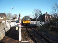 The guard has operated the level crossing barriers from the platform at Moss Side and 142003 departs for Kirkham on a Colne service. In the other direction the half barriers are activated automatically by the approaching train.<br><br>[Mark Bartlett&nbsp;07/02/2009]