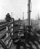Looking west from Geilston level crossing, Cardross, in March 1974 as a Class 303 unit disappears into the distance towards Helensburgh. Note the LNER lamp housing on top of the gate.<br> <br><br>[John McIntyre&nbsp;/03/1974]