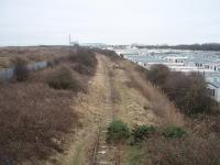 View south from the end of the rails on the former Fleetwood line towards Burn Naze, where the industrial complex that kept the southern section of the line open for freight until the 1990s can be seen. Right up to the 1960s this then double track line saw express fish trains to London as well as a variety of other traffic. Passenger services ceased in 1970. Map Ref SD 329455<br><br>[Mark Bartlett&nbsp;17/02/2009]