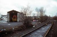 The <I>Nickey Line</I> between Hemel Hempstead and Harpenden carried traffic until 1979 when the Hemelite building block factory at the western end switched to road transport to import its raw materials. Shown here are the factory sidings at Cupid Green near Hemel Hempstead a few months before the rail traffic ceased, complete with the company's Ruston loco tucked away in its shed for the Christmas break. Appropriately, the shed is built from <I>Hemelite</I> aggregate blocks.<br><br>[Mark Dufton&nbsp;26/12/1978]