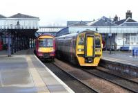 170 478 is halted at Stirling with a Glasgow to Dunblane service while Alphaline-liveried 158 871 pulls out for Edinburgh on 4 March 2009.<br><br>[David Panton&nbsp;04/03/2009]