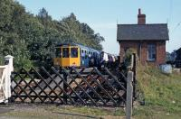 In the late 1970s, the former Midland and Great Northern station at Lenwade had a regular passenger service, albeit one visit a year from a succession of special excursions. This is the 1978 trip, in the form of a Birmingham/Cravens DMU chartered by the Aylsham and District Railway Action Committee. Despite the heroic local efforts, the line from Lenwade to Wroxham was closed and dismantled in the early 1980s. The station building survives, sensitively restored as a private family house.<br><br>[Mark Dufton&nbsp;16/09/1978]