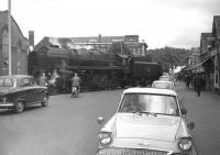 BR Standard class 9F 2-10-0 no 92239 crosses the road on its way out of Southampton Docks in 1963, just as a boy-racer of the day revs his Ford Anglia for the off.... (after donning his <I>shades</I>).<br><br>[Robin Barbour Collection (Courtesy Bruce McCartney)&nbsp;17/07/1963]
